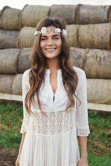 Frau, die stilvolles weißes kleid auf dem land trägt