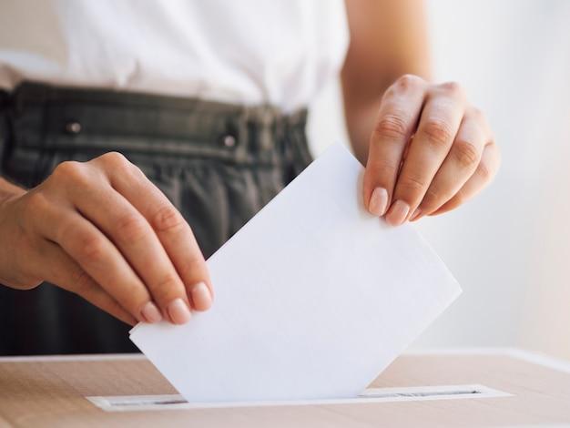 Frau, die stimmzettel in kasten legt