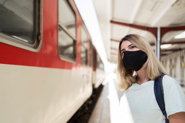 Frau, die stoffmaske trägt, die neben dem zug steht