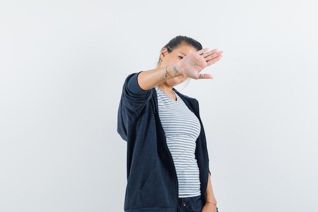 Frau, die stoppgeste im t-shirt zeigt