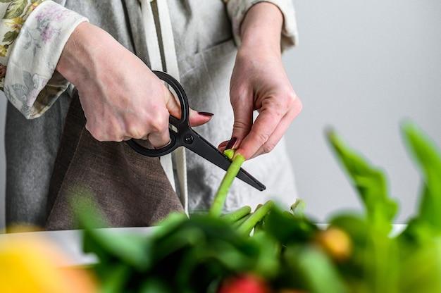 Frau, die strauß frischer blumen macht. strauß gelber, orange und roter tulpen