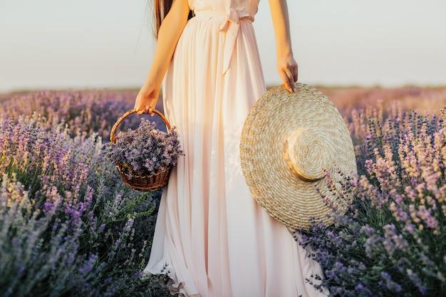Frau, die strohhut und strohkorb im lavendelfeld hält.