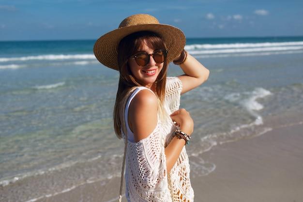 Frau, die strohsack hält und auf dem strand geht