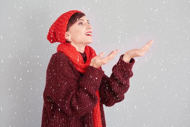 Frau, die stücke des ersten schnees fängt