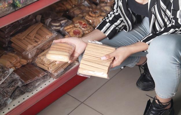 Frau, die süßigkeiten im supermarkt wählt
