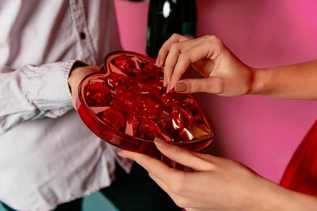 Frau, die süßigkeiten in der kastenform des herzens von ihrem freund am valentinstag erhält.