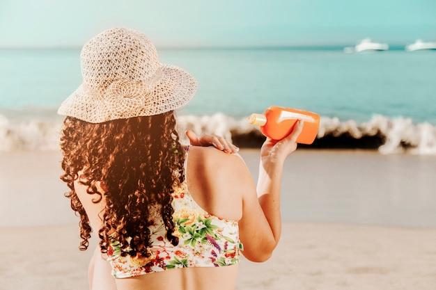 Frau, die sunblock am strand anwendet