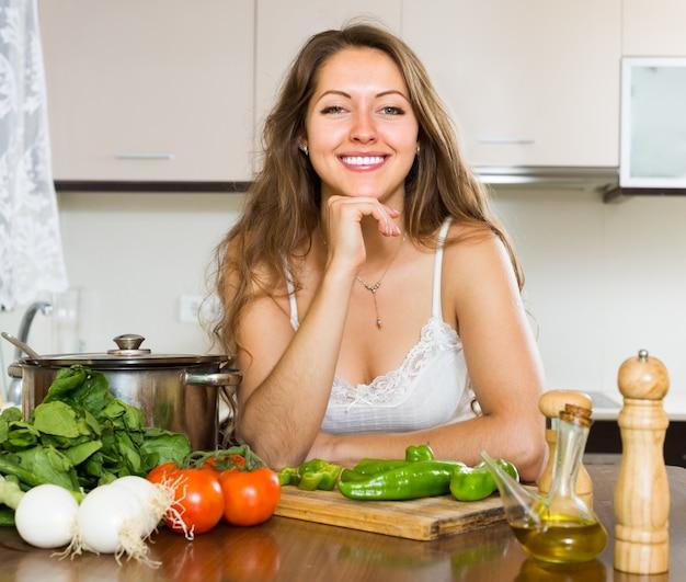 Frau, die suppe in der küche kocht