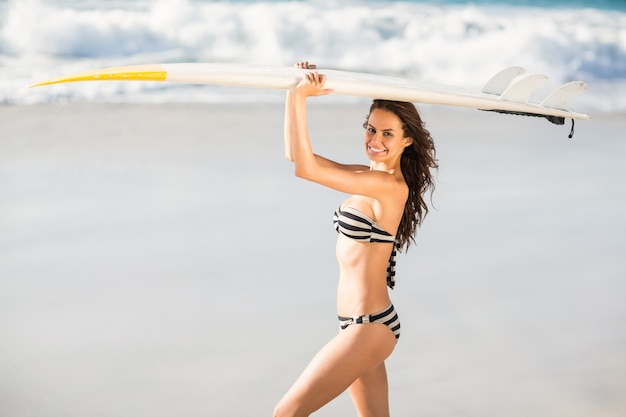 Frau, die surfbrett am strand hält