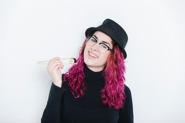 Frau, die sushi mit stäbchen für gesundes essen isst