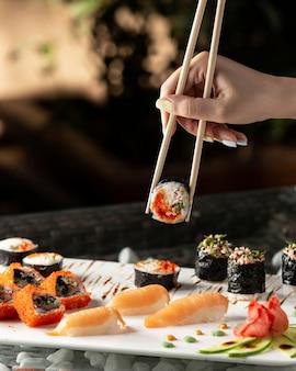 Frau, die sushi-rolle mit stäbchen hält