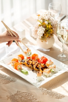 Frau, die sushi-rollen mit stäbchen nimmt