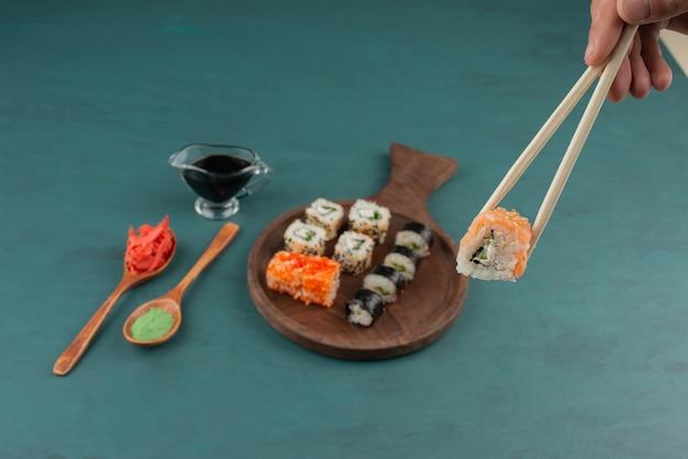 Frau, die sushirolle mit stäbchen auf blauem tisch mit eingelegtem ingwer und sojasauce hält.