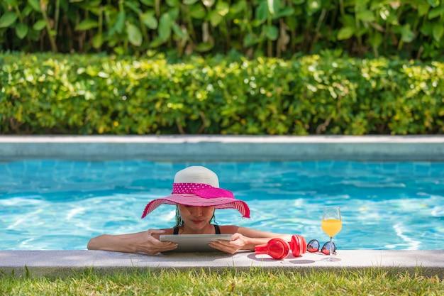 Frau, die tablet-computer im pool verwendet