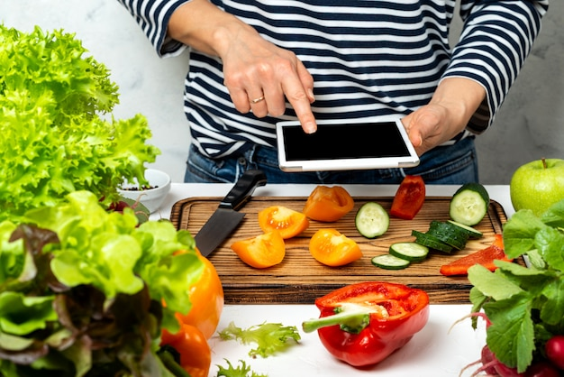 Frau, die tablet-computer mit leerem bildschirm in der hand kocht und hält