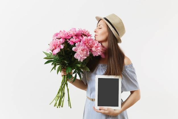 Frau, die tablet-computer mit leerem leerem bildschirm hält, um raum zu kopieren, blumenstrauß der schönen rosa pfingstrosenblumen lokalisiert auf weißem hintergrund spott oben. online-shopping-konzept für die lieferung von unternehmen. werbefläche