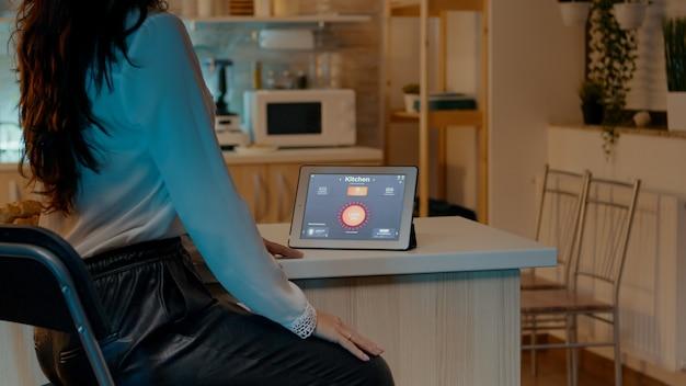 Frau, die tablet im haus mit automatisierungsbeleuchtungssystem betrachtet