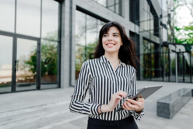 Frau, die tablette außerhalb des firmengebäudes verwendet