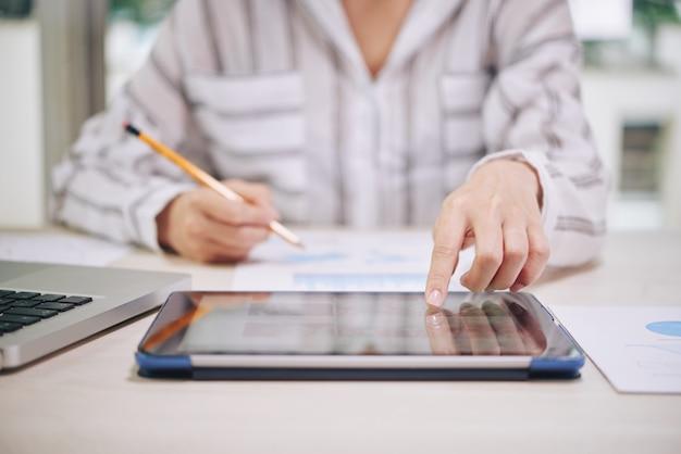 Frau, die tablette beim arbeiten verwendet