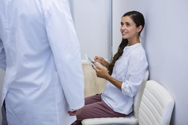 Frau, die tablette beim betrachten des zahnarztes hält