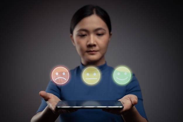 Frau, die tablette hält und emoticon-hologrammeffekt zeigt
