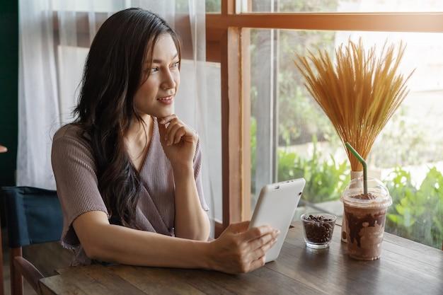 Frau, die tablette im café denkt und verwendet