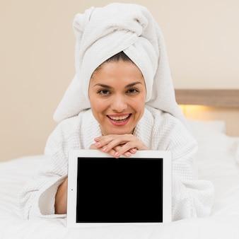 Frau, die tablette im hotelzimmer darstellt