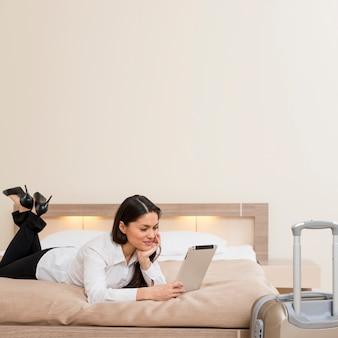 Frau, die tablette im hotelzimmer verwendet