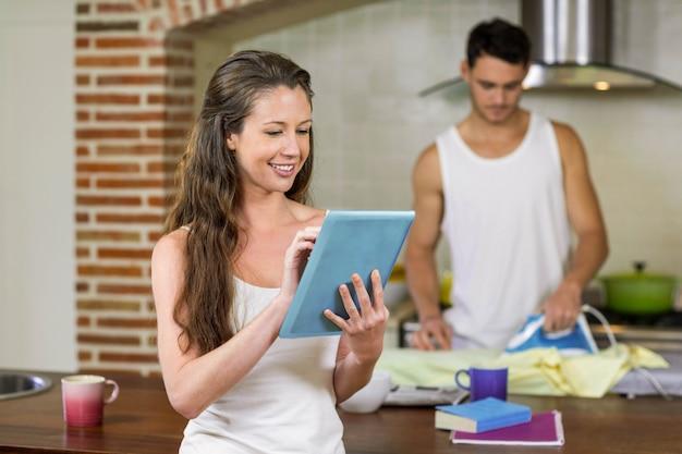 Frau, die tablette in der küche während mann bügelt ein hemd im hintergrund verwendet