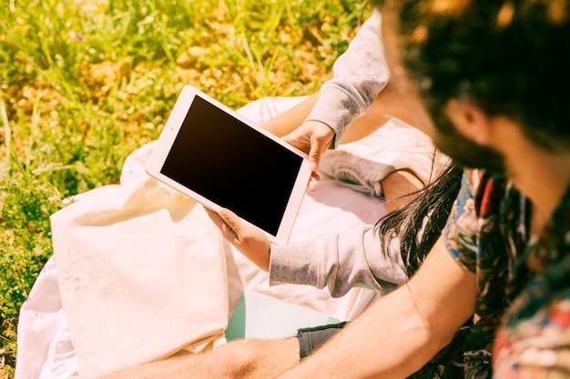 Frau, die tablette in der wiese hält