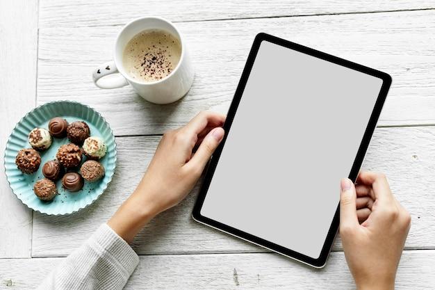 Frau, die tablette mit leerem bildschirm von zu hause aus arbeitet
