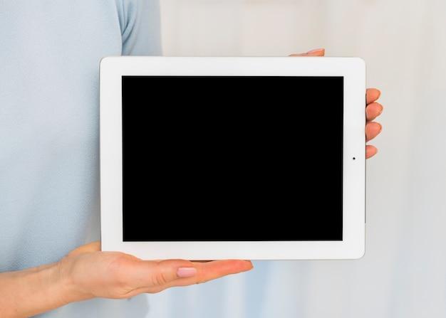 Frau, die tablette mit schwarzem leerem bildschirm hält