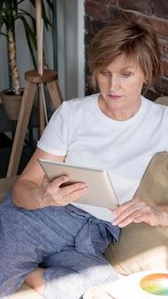 Frau, die tablette mittlerer schuss hält