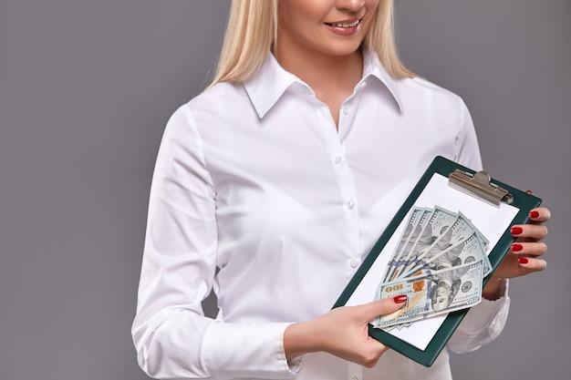 Frau, die tablette und dollar bargeld hält und an der kamera zeigt.