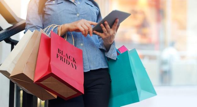 Frau, die tablette verwendet und black friday-einkaufstasche bei der stellung auf der treppe mit hält
