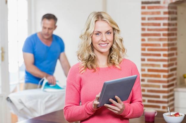 Frau, die tablette während ehemann verwendet eisen im wohnzimmer verwendet