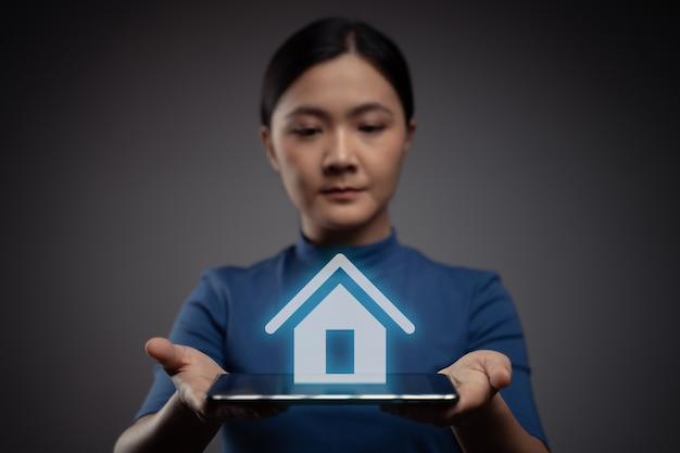 Frau, die tablette zeigt, die mit hauptikonenhologrammeffekt zeigt