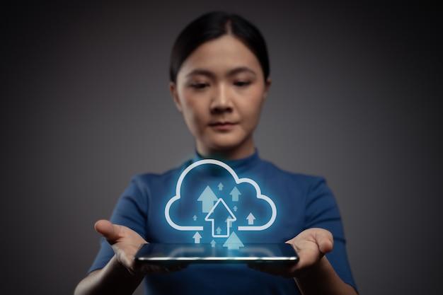 Frau, die tablette zum hochladen mit wolkensymbolhologrammeffekt verwendet