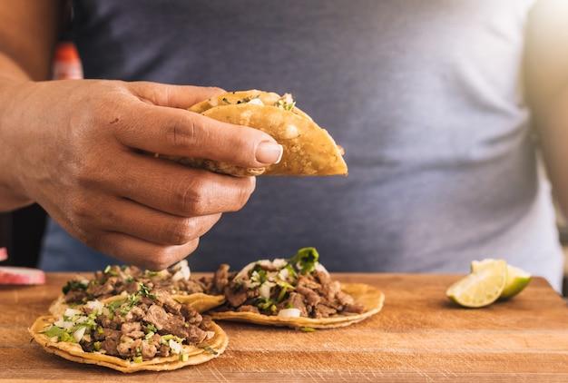 Frau, die taco mit gelber maistortilla hält