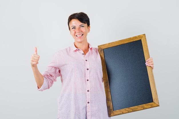 Frau, die tafel hält, daumen oben im rosa hemd zeigt und fröhlich schaut. vorderansicht.
