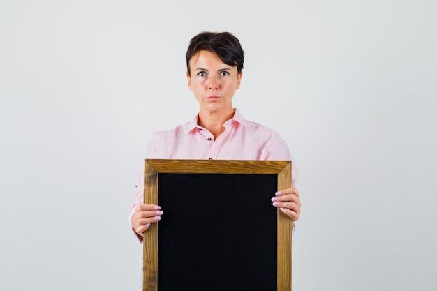 Frau, die tafel im rosa hemd hält und ernst schaut. vorderansicht.