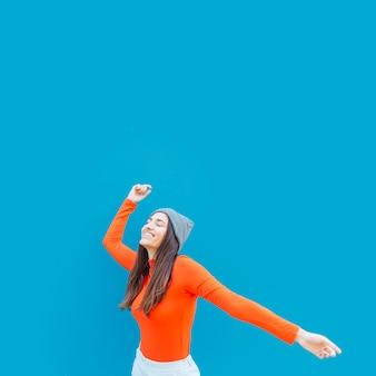 Frau, die tanz gegen blaue oberfläche genießt