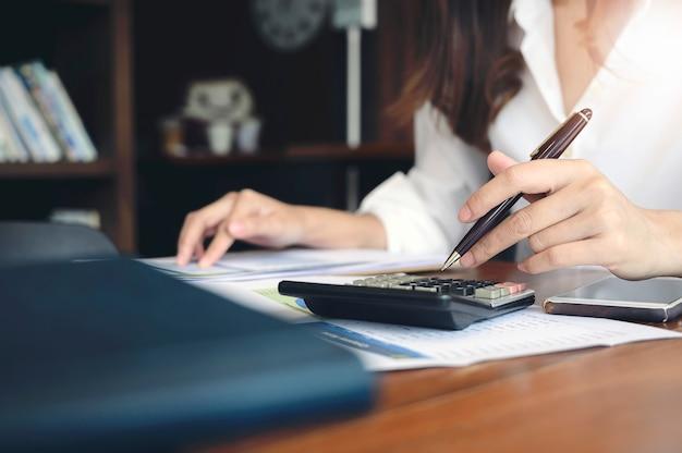 Frau, die taschenrechner am schreibtisch verwendet.