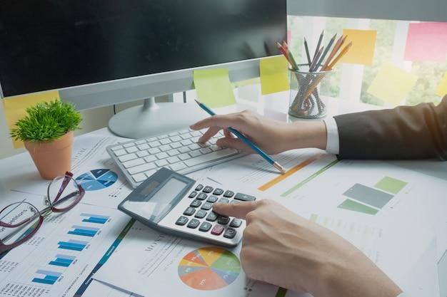 Frau, die taschenrechner beim arbeiten für finanzdokumente verwendet