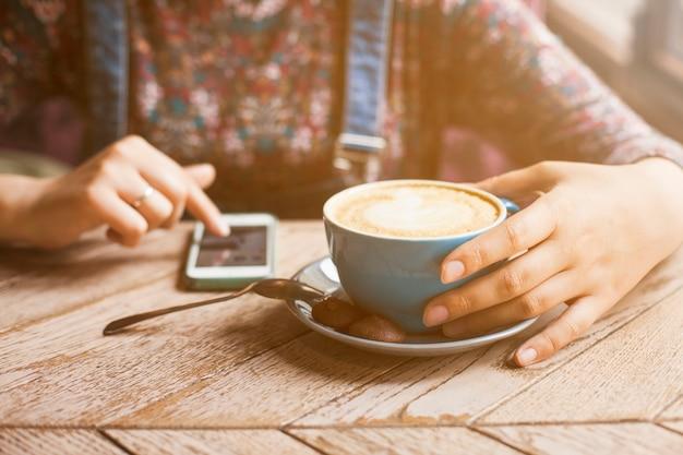 Frau, die tasse kaffee bei der anwendung des mobiltelefons hält