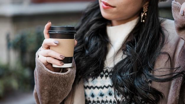 Frau, die tasse kaffee draußen hält