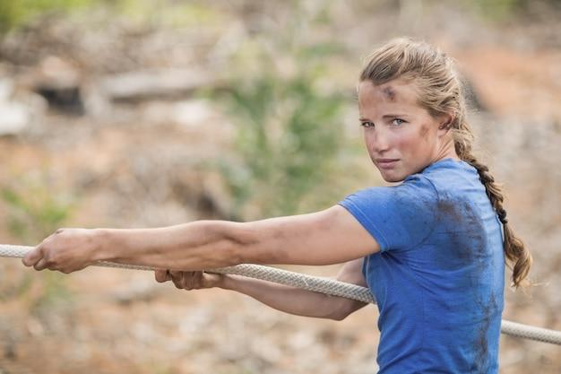 Frau, die tauziehen während des hindernislaufs im bootcamp spielt