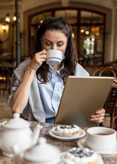 Frau, die tee beim betrachten auf einer tablette trinkt