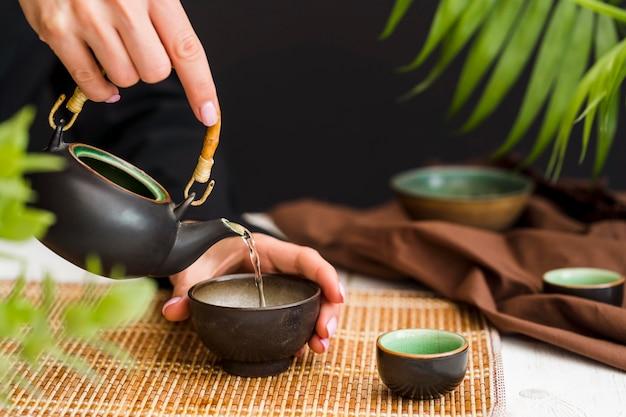Frau, die tee in tasse mit teekanne gießt