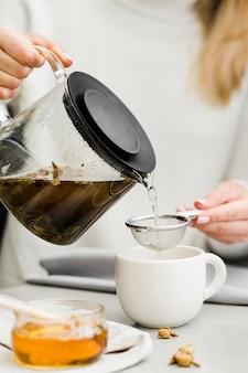 Frau, die tee in tasse von teebrauer unter verwendung des siebs gießt